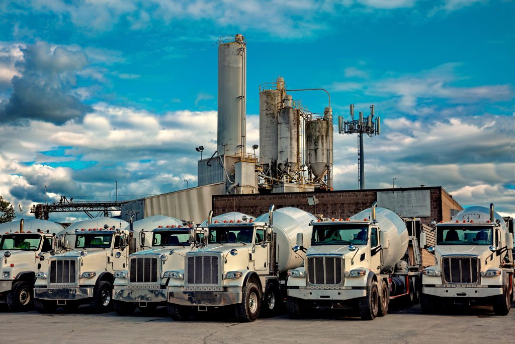 A range of cement mixer trucks  in a parking lot of a cement factory.